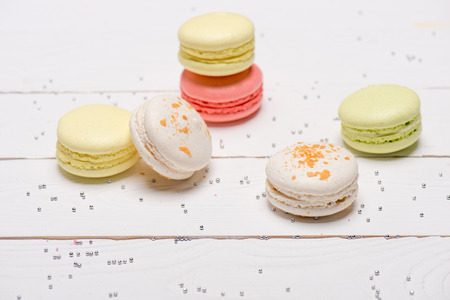 Group of beautiful colorful macarons on white wooden table. Sweets background