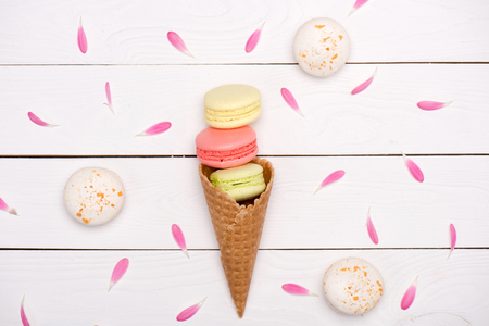 Pink flower petals around of handmade fresh macarons in waffle cone on wooden surface.   macarons background concept Stock Photo
