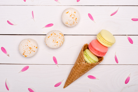 Top view of pink flower petals around handmade fresh macarons in waffle cone. macarons background concept Stock Photo