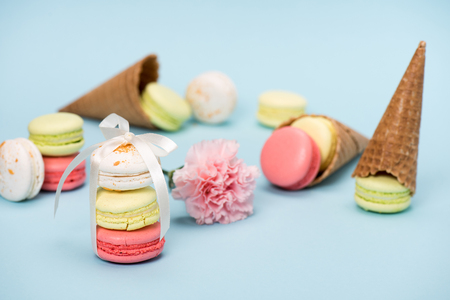 Colorful macarons tying with white ribbon for gift on blue surface. Still life of macarons with flower and waffle cones. sweets background concept