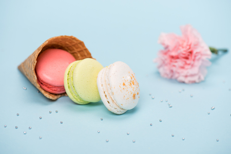 Group of handmade macarons in waffle cone and pink flower on blue surface. macarons background concept Stock Photo