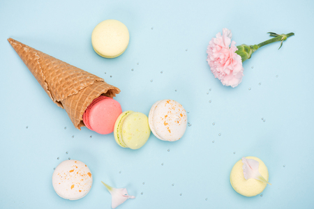 Top view of sweet macarons in waffle cone with pink Carnation. Colorful sweets background