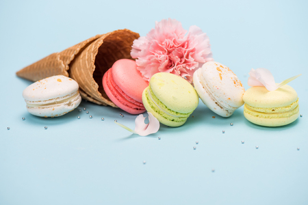Group of handmade macarons in waffle cone and pink flower on blue surface. macarons background concept Imagens