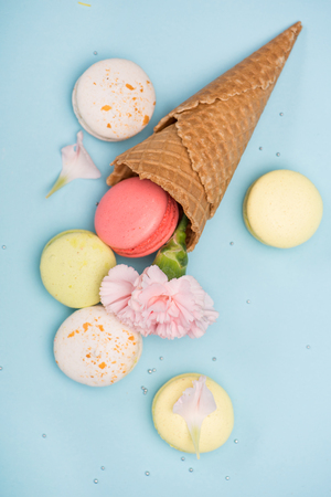 Top view of sweet macarons in waffle cones with pink Carnation. Colorful sweets background