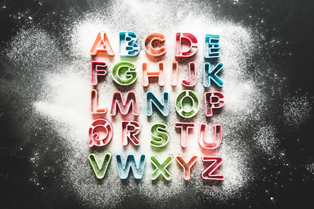 throe: top view of baking forms for cookies in forms of letters with floor on tabletop, baking cookies Stock Photo