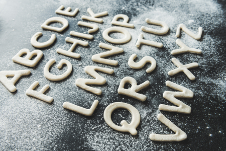 throe: close up of dough for cookies in forms of letters with powdered sugar, cookie dough
