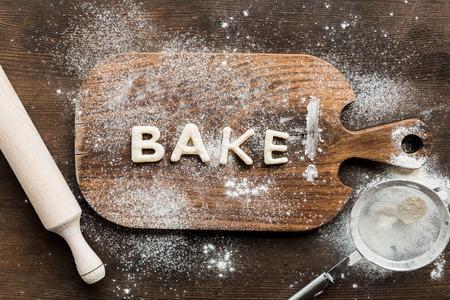 쿠키 개념을 베이킹 나무 커팅 보드에 반죽에서 만든 식용 문자 베이킹의 상위 뷰