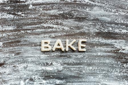 Vista superior de la palabra hornear hecha de masa de galletas con harina en la superficie de madera Foto de archivo - 79760014