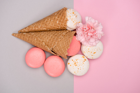 Top view of macarons with waffle cones and Carnation flower on colorful background. macarons background concept