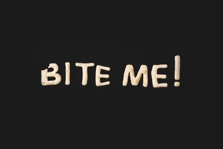 Vista superior de letras morderme hecho de masa de galletas aislada en negro Foto de archivo - 79760164
