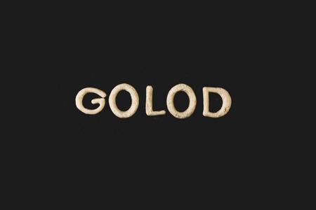 Vista superior de la palabra golod hecha de masa para galletas aislada en negro Foto de archivo - 79760165