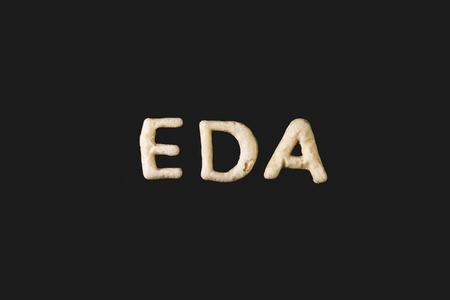 Vista superior de la palabra eda hecha de masa para galletas aislada en negro Foto de archivo - 79760175