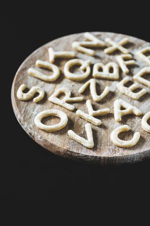 Cerrar vista de letras hechas de masa de galletas en el tablero de madera con harina aislada en negro Foto de archivo - 79760005