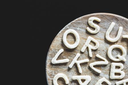 Vista superior de las letras hechas de masa de galletas en el tablero de madera con harina aislada en negro Foto de archivo - 79760007