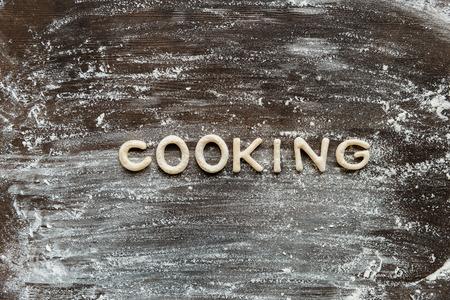 Vista superior de la palabra cocina hecha de masa de galletas con harina en la superficie de madera Foto de archivo - 79760008