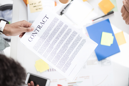 homeoffice: businessman holding contract above table with papers