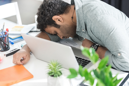casual businessman sleeping on the table near laptop at modern office Stock Photo