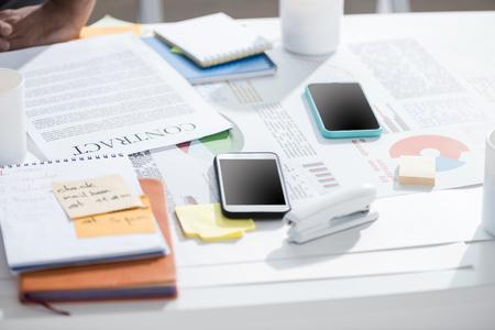 スマート フォン契約と近代的なオフィスでテーブルにホッチキスのノートブック 写真素材 - 79832497