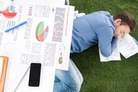 homeoffice: Young businessman sleeping on green grass carpet at modern office