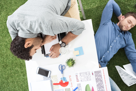 Young businessmen sleeping on the table and green grass carpet at modern office