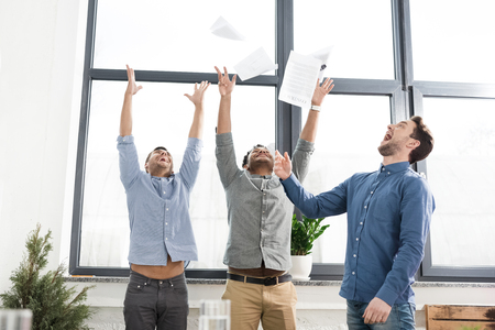 triumphing: Cheerful young businessmen triumphing and throwing papers in office