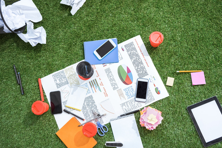 homeoffice: heap of business objects and office supplies laying on green grass carpet at office