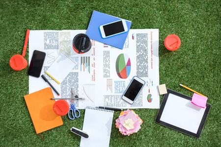 hoop bedrijfsobjecten en kantoorbenodigdheden die op groen grastapijt leggen op kantoor
