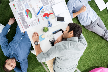 homeoffice: Young businessmen sleeping on the table and green grass carpet at modern office
