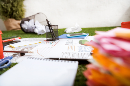 heap of business objects and office supplies laying on green grass carpet at office