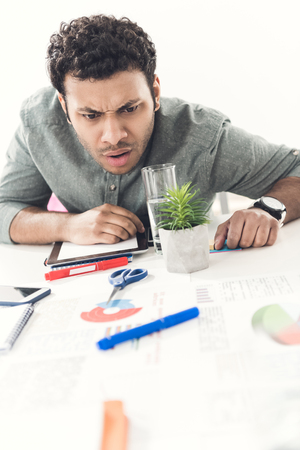 young tired casual businessman sitting at table in office Stock Photo