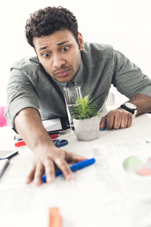 homeoffice: young tired casual businessman sitting at table in office Stock Photo