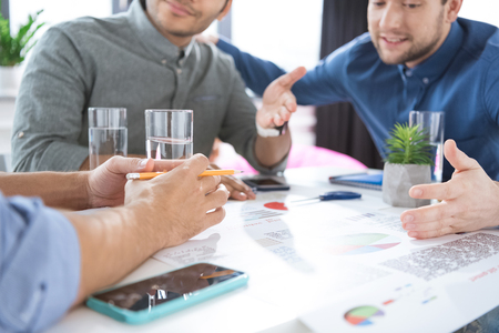 homeoffice: young businessmen drinking water and discussing new project, business teamwork concept Stock Photo
