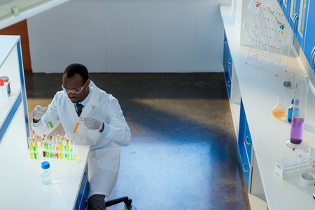 african american scientist working with test tubes in chemical laboratory