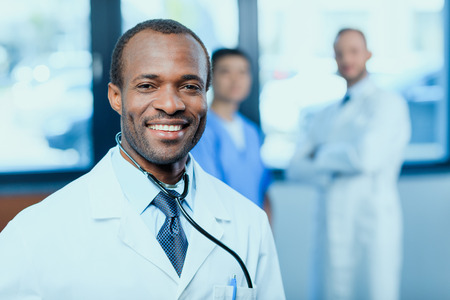 smiling doctor with stethoscope with colleagues behind in clinic