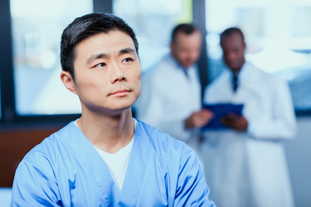 thoughtful doctor in medical uniform with collegues behind in clinic