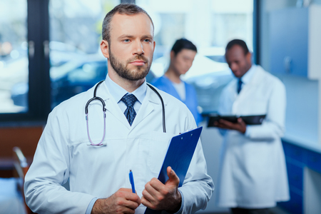 confident doctor holding folder in clinic with colleagues behind