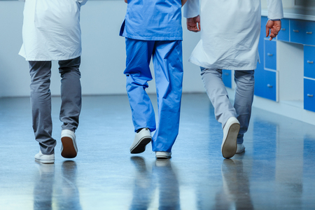 partial view of group of doctors walking in clinic, Stock Photo