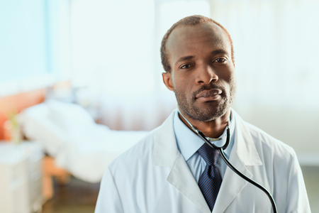 serious doctor with stethoscope standing in hospital chamber Stock Photo