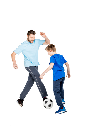 father and son playing soccer isolated on white