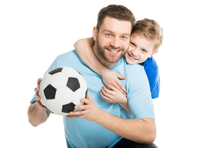 father and son posing with soccer ball isolated on white Imagens
