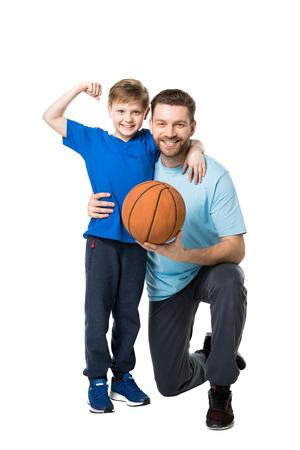 Lächelnder Vater und Kind bereit, Basketball zu spielen. Junge zeigt seinen Bizeps