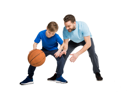 Father with son in casual clothes playing basketball