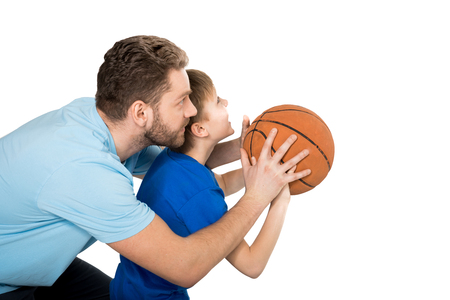 father with son playing basketball isolated on white