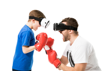 side view of father and son boxing in virtual reality headsets Фото со стока