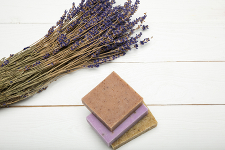 Close-up view of homemade soap pile with dried lavender bunch on wooden surface Stock Photo