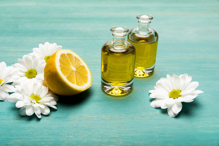 Close-up view of essential oil in bottles with sliced lemon and chamomiles on blue wooden table