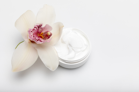 Close-up view of organic cream in container with orchid isolated on white