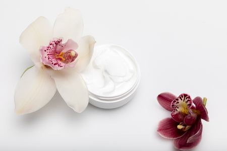 Close-up view of organic cream in container with orchids isolated on white