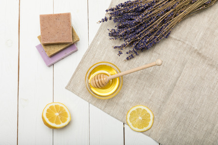 Close-up view of homemade soap collection with dried lavender flowers, sliced lemon and honey
