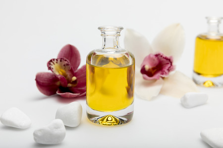 Close-up view of essential oil, white stones and orchids isolated on white